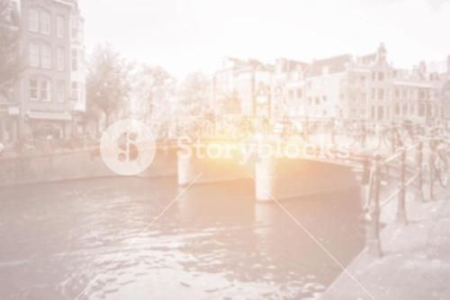 Amsterdam canal bridge with bright light and bicycles
