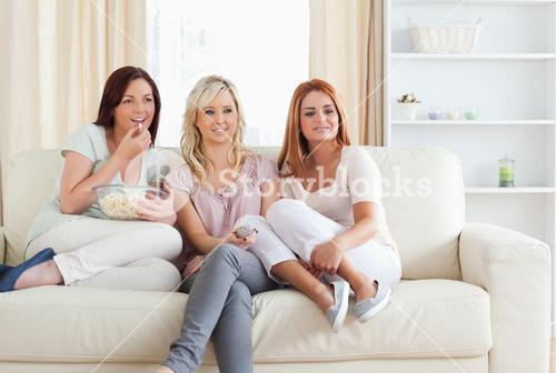 Happy Women watching a movie eating popcorn