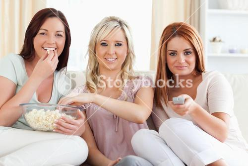 Laughing young Women watching a movie eating popcorn