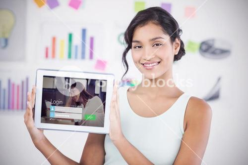 Composite image of happy businesswoman showing digital tablet in creative office