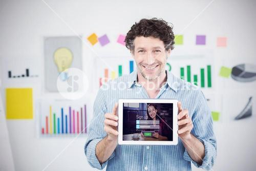 Composite image of businessman showing digital tablet with blank screen in creative office