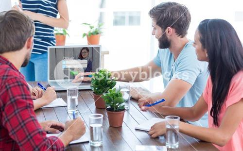 Composite image of business team using a laptop