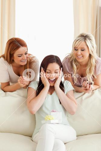 Smiling women giving their friend a present