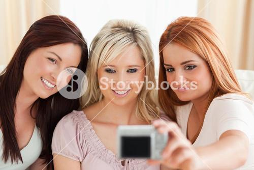 Smiling women lounging on a sofa with a camera