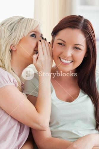 Smiling young woman telling her friend a secret