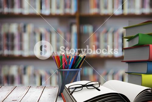 school materials on table with library background