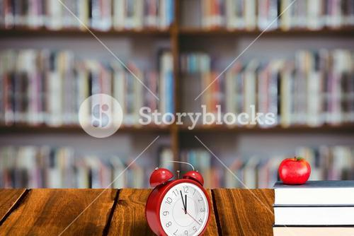 Stack of books with red apple and alarm clock on library background