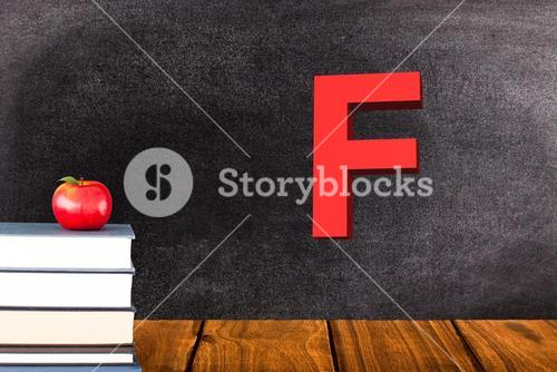 stack of books and red apple on chalkboard background with F grade