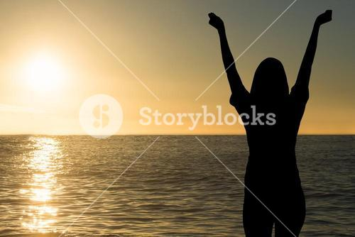 cheering silhouette on sea sunset background