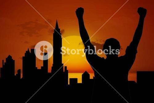 silhouette of cheering person with city and sunset background
