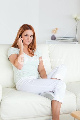 Woman sitting on a sofa with a cellphone
