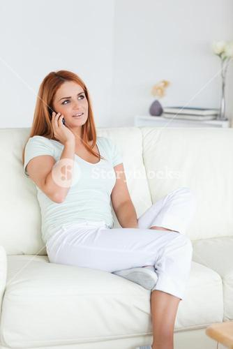 Young Woman sitting on a sofa with a cellphone