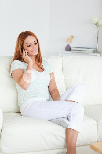 Young Woman sitting on a sofa with a phone