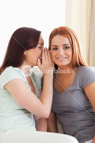 Cute woman being told a secret