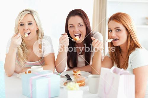 Goodlooking Women sitting at a table eating a cake