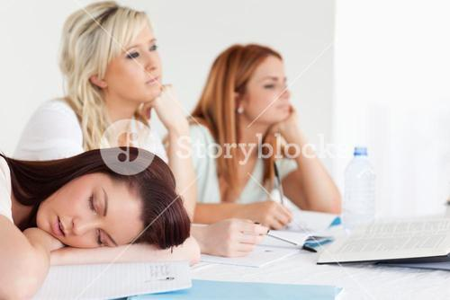 Bored university students one sleeping sitting at a table