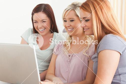 Smiling women sitting on a sofa with a laptop