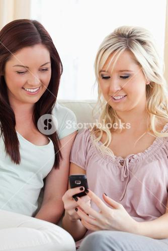 Women sitting on a sofa with a phone