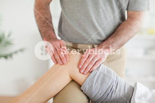 Male Chiropractor massaging a charming womans knee