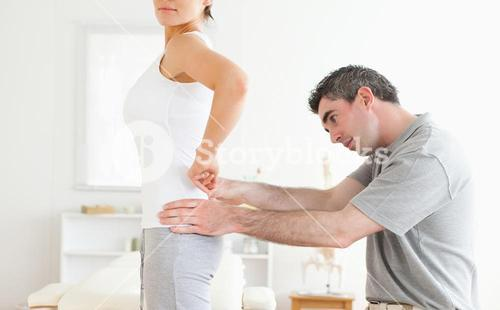 Chiropractor examining a cute womans back