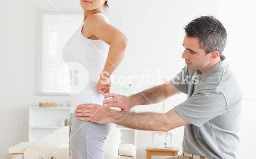 Chiropractor examining a charming womans back