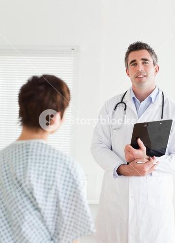 Doctor talking to a charming woman in hospital gown