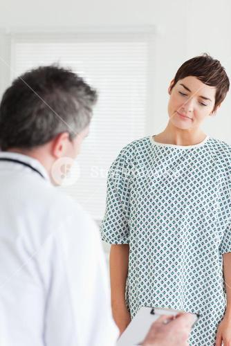 Woman in hospital gown talking to her doctor