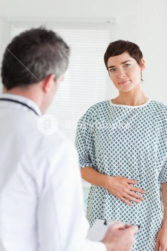 Charming Woman in hospital gown talking to her doctor
