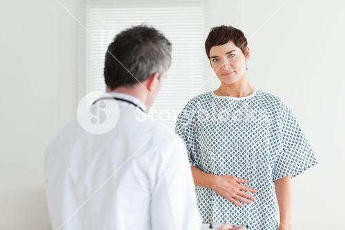 Brunette Woman in hospital gown talking to her doctor