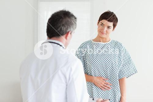 Young Woman in hospital gown talking to her doctor