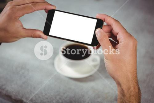 Hands taking photograph of coffee