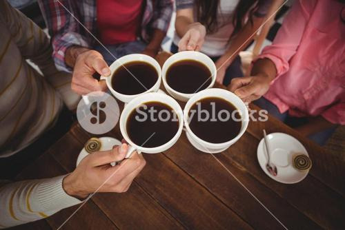 Group of friends toasting cup of coffee