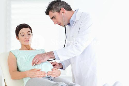 Doctor examining the cute womans tummy with a stethoscope