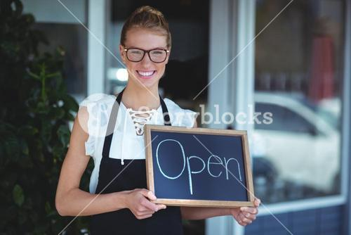 Portrait of waitress standing with chalkboard