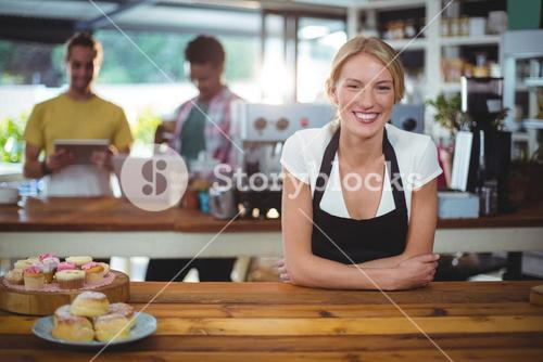 Portrait of waitress standing behind the counter