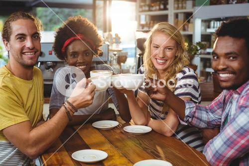 Group of happy friends holding cup of coffee