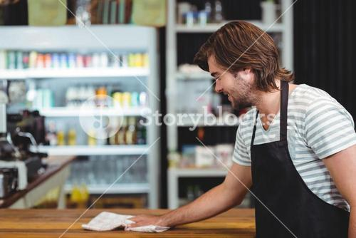 Smiling waiter cleaning cafe counter