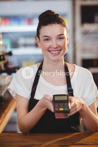 Smiling waitress showing credit card machine