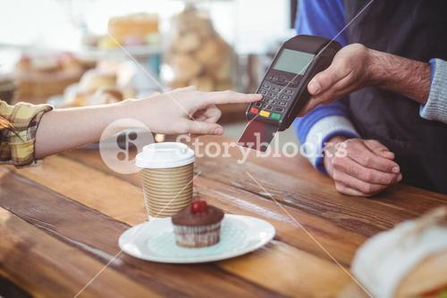 Customer entering pin number into machine at counter