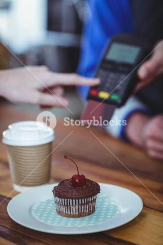 Plate of cupcake and coffee at counter