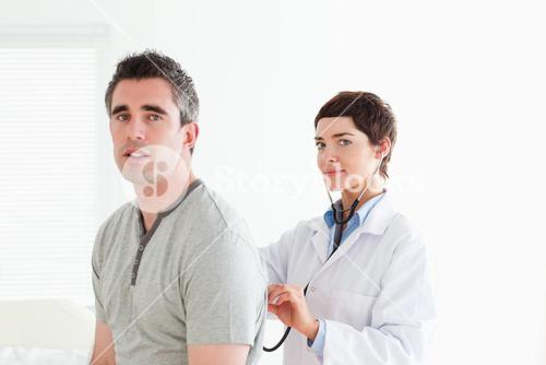 Charming Doctor examining a patient with a stethoscope
