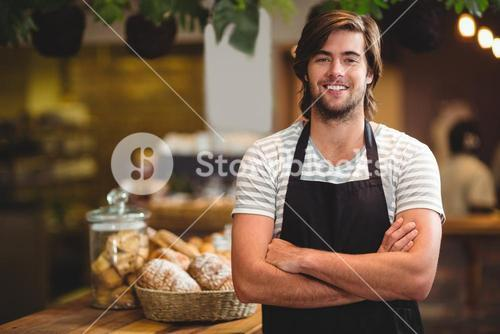 Portrait of smiling waiter standing with arm crossed