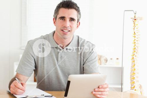 Male Doctor sitting working with a tablet and a chart