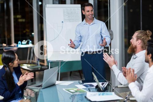 Coworkers applauding a colleague after presentation