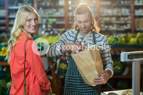 Man assisting woman in selecting vegetables