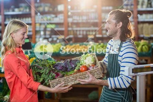 Male staff giving a crate of fresh vegetables to woman in organic section