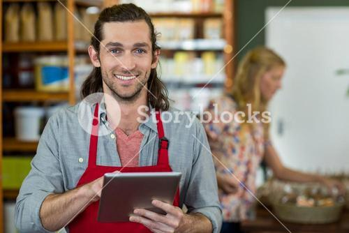 Male staff holding a digital tablet and checking grocery products on the shelf