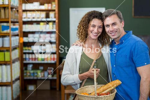 Portrait of happy couple standing with a basket