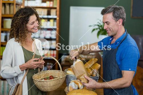 Smiling woman purchasing bread at bakery store