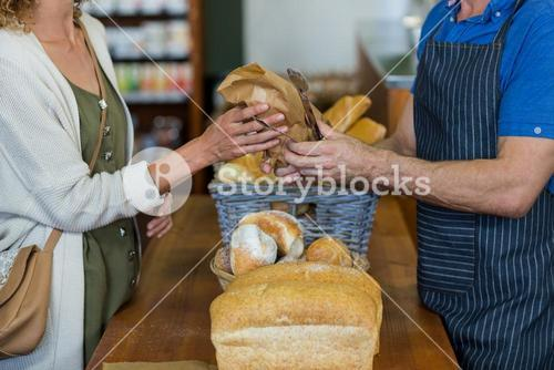 Mid section of woman purchasing bread at bakery store